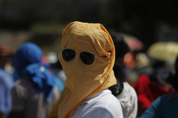 A student from Ayotzinapa Teacher Training College student wears a mask during a roadblock to demand the safe return of students who went missing on September 26, on the outskirts of Chilpancingo